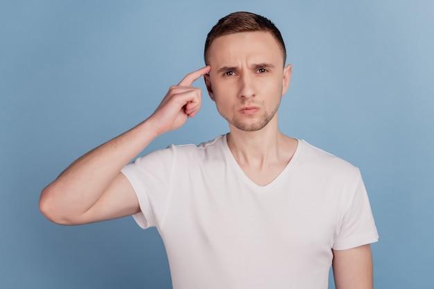 Jeune bel homme portant des vêtements décontractés pointant vers la tête du doigt pense que la mémoire se souvient d'isolé sur fond de couleur bleu