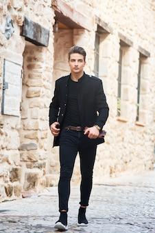 Jeune bel homme portant des vêtements noirs