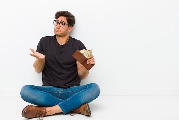 Jeune bel homme avec un portefeuille assis sur le sol, assis sur le sol dans une salle blanche