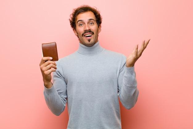 Jeune bel homme avec un portefeuille contre un mur plat rose
