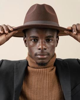 Jeune bel homme posant avec chapeau
