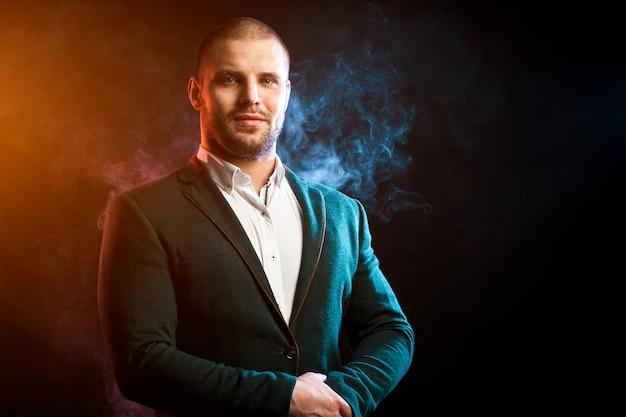 Jeune bel homme posant contre la fumée rouge et bleue
