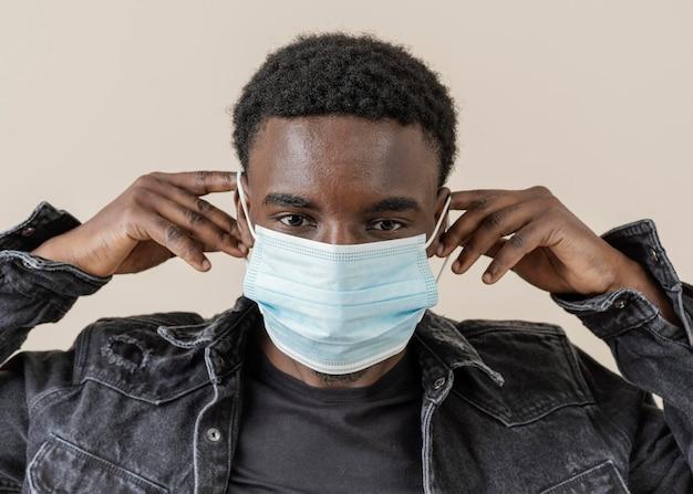 Jeune bel homme posant avec masque