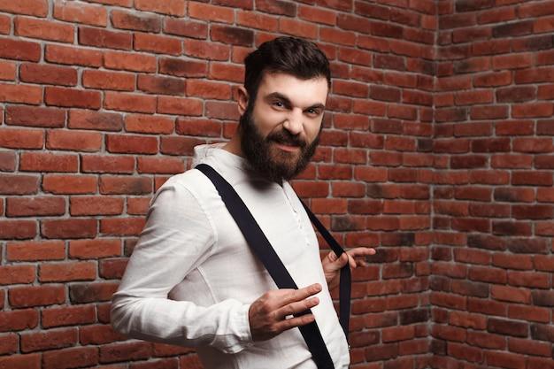 Jeune bel homme posant sur le mur de briques.