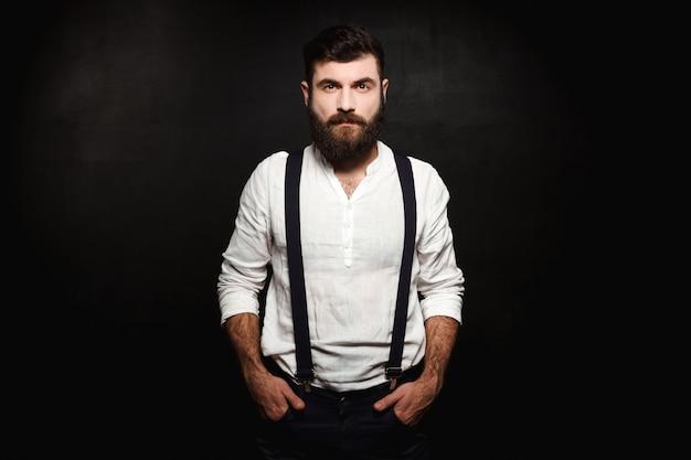 Jeune bel homme posant sur noir.