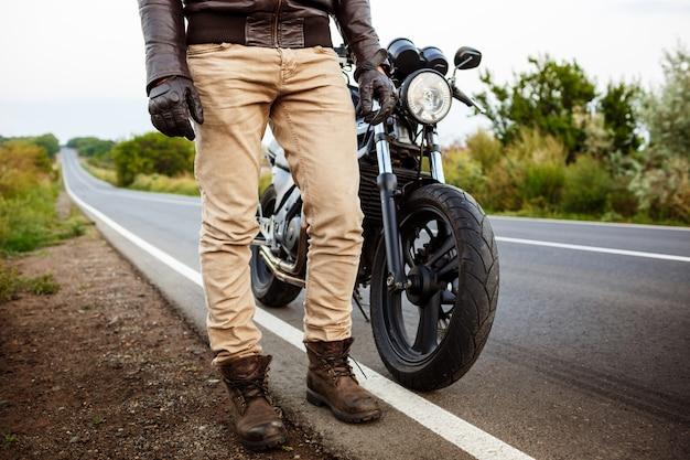Jeune bel homme posant près de sa moto à la route de campagne.