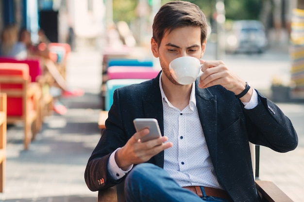 Jeune bel homme profiter du café travaillant sur ordinateur portable