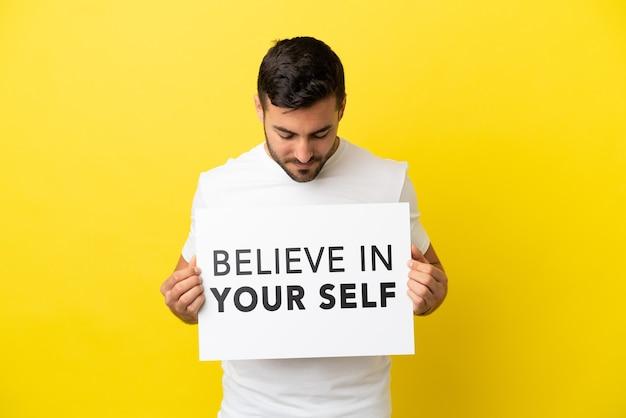 Jeune bel homme de race blanche isolé sur fond jaune tenant une pancarte avec texte croyez en vous-même
