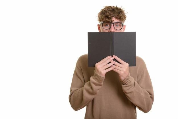 Jeune bel homme de race blanche se cachant derrière un livre