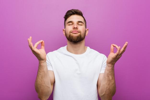 Jeune bel homme de race blanche se détend après une dure journée de travail, il effectue du yoga.