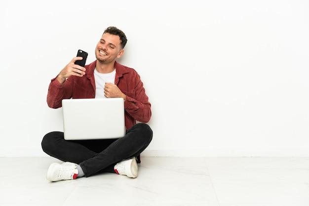 Jeune bel homme de race blanche sit-in sur le sol avec un ordinateur portable faisant un selfie