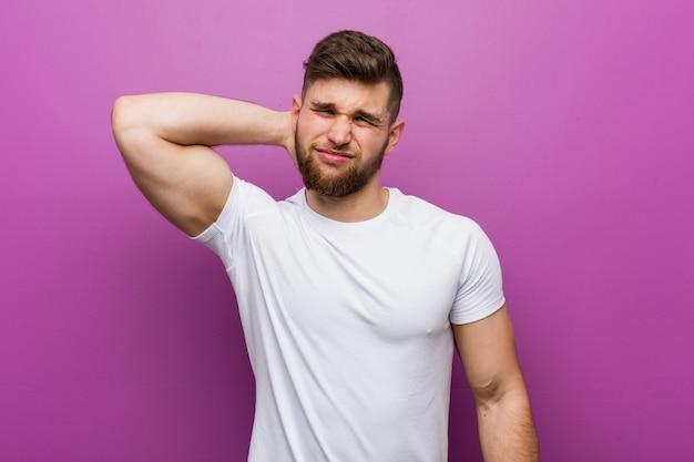 Jeune bel homme de race blanche souffrant de douleurs au cou en raison de la vie sédentaire.