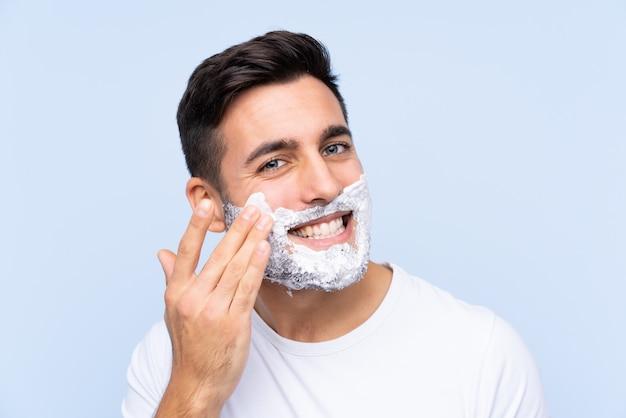 Jeune bel homme rasant sa barbe sur un mur isolé
