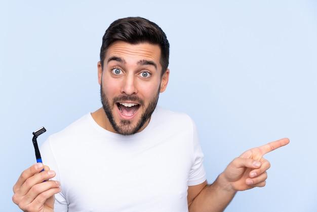 Jeune bel homme rasant sa barbe surpris et pointant le doigt sur le côté