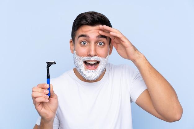 Jeune bel homme rasant sa barbe avec surprise et expression faciale choquée