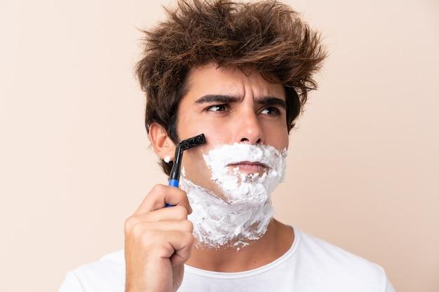 Jeune bel homme rasant sa barbe