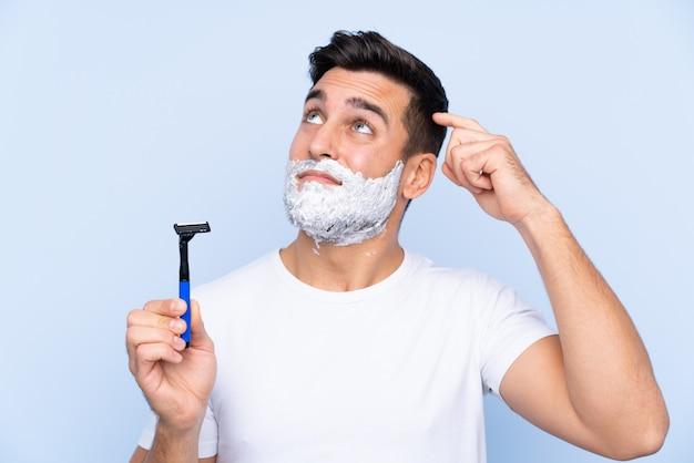 Jeune bel homme raser sa barbe ayant des doutes et avec une expression de visage confuse