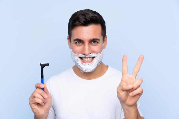 Jeune bel homme raser sa barbe en souriant et en montrant le signe de la victoire