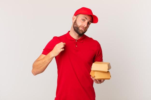 Jeune bel homme à la recherche d'un concept de livraison de hamburger arrogant, réussi, positif et fier