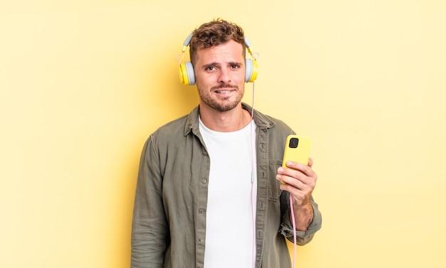Jeune bel homme à la recherche d'écouteurs perplexes et confus et concept de smartphone