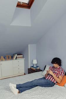 Jeune bel homme à la recherche de smartphone et se reposant sur un lit. concept de temps libre à la maison.