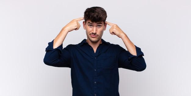 Jeune bel homme avec un regard sérieux et concentré, brainstorming et réflexion sur un problème difficile