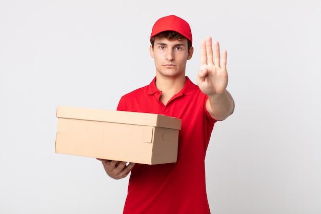 Jeune bel homme regardant sérieux montrant la paume ouverte faisant le concept de service de paquet de livraison de geste d'arrêt.