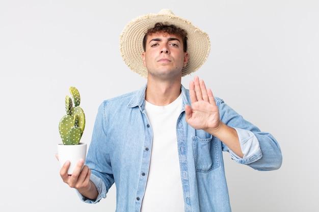 Jeune bel homme regardant sérieux montrant la paume ouverte faisant un geste d'arrêt. agriculteur tenant un cactus décoratif