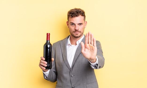 Jeune bel homme regardant sérieux montrant la paume ouverte faisant un geste d'arrêt. concept de bouteille de vin