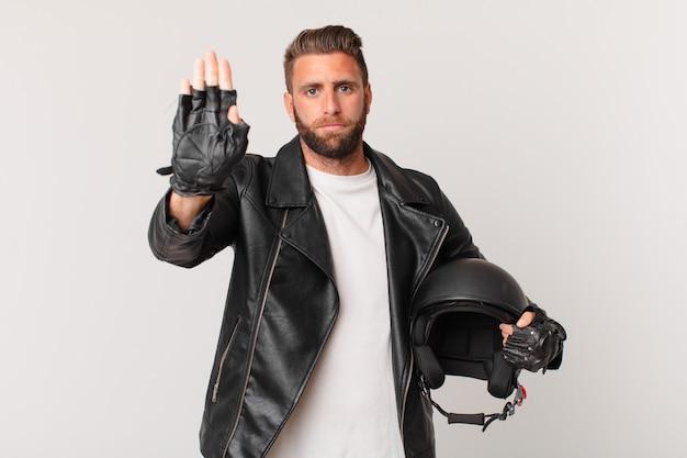 Jeune bel homme regardant sérieux montrant la paume ouverte faisant un geste d'arrêt. concept de casque de moto