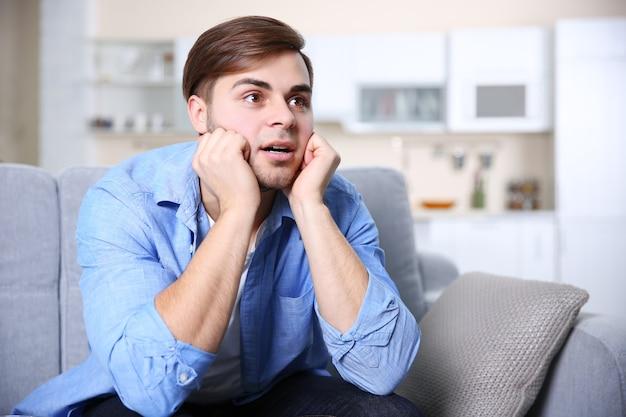 Jeune bel homme regardant la télévision sur un canapé à la maison