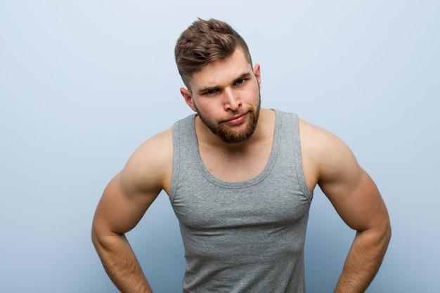 Jeune bel homme de remise en forme gronde quelqu'un très en colère