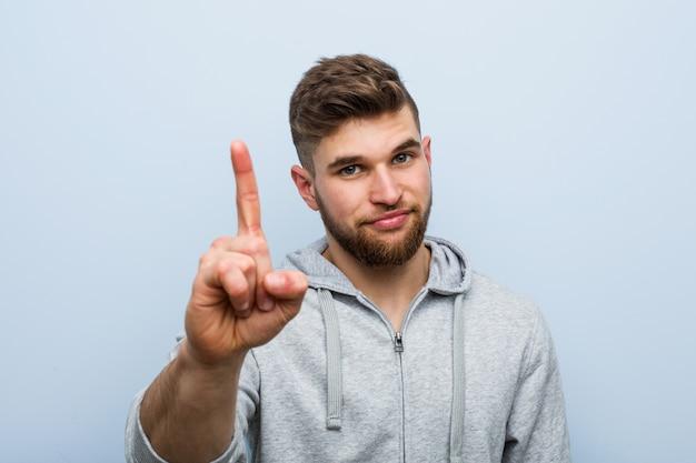 Jeune bel homme de remise en forme, montrant le numéro un avec le doigt.