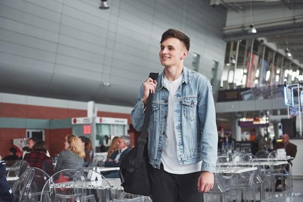Jeune bel homme avec un sac sur son épaule pressé de l'aéroport.