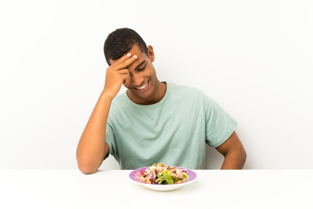 Jeune bel homme avec une salade dans une table en riant
