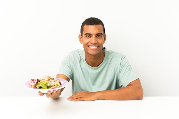 Jeune bel homme avec une salade dans une table