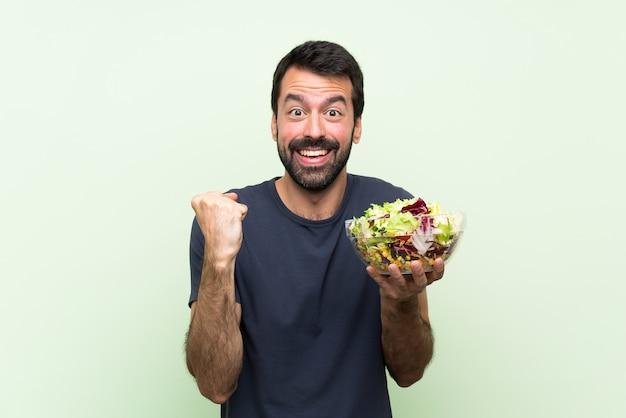 Jeune bel homme avec une salade sur le mur vert isolé, célébrant une victoire en position de gagnant