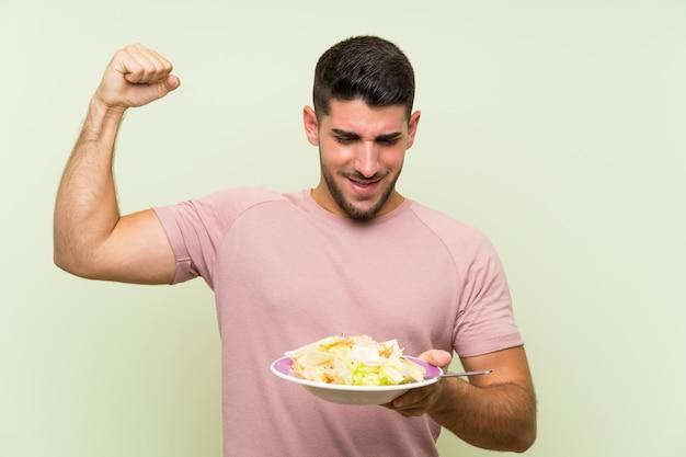 Jeune bel homme avec une salade sur le mur vert isolé célébrant une victoire