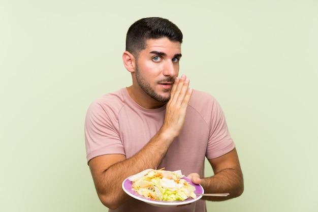 Jeune bel homme avec une salade sur mur vert isolé, chuchotant quelque chose