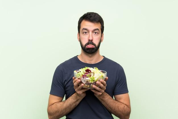Jeune bel homme avec une salade sur un mur vert isolé avec une expression triste et déprimée