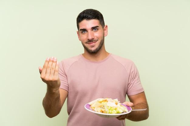 Jeune bel homme avec une salade sur le mur vert isolé invitant à venir avec la main. heureux que tu sois venu