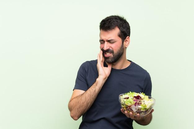 Jeune bel homme avec salade sur mur vert isolé avec maux de dents