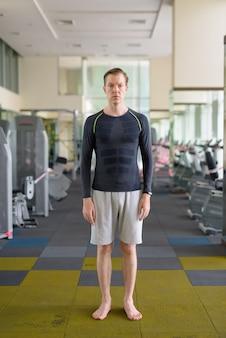 Jeune bel homme à la salle de gym pendant covid-19