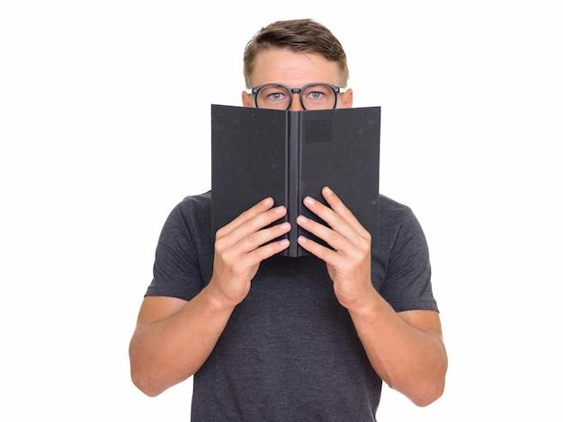 Jeune bel homme se cachant derrière livre
