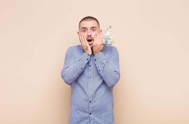Jeune bel homme se sentant choqué et effrayé, l'air terrifié avec la bouche ouverte et les mains sur les joues avec des billets en dollars