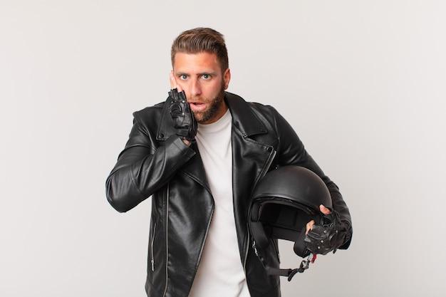Jeune bel homme se sentant choqué et effrayé. concept de casque de moto