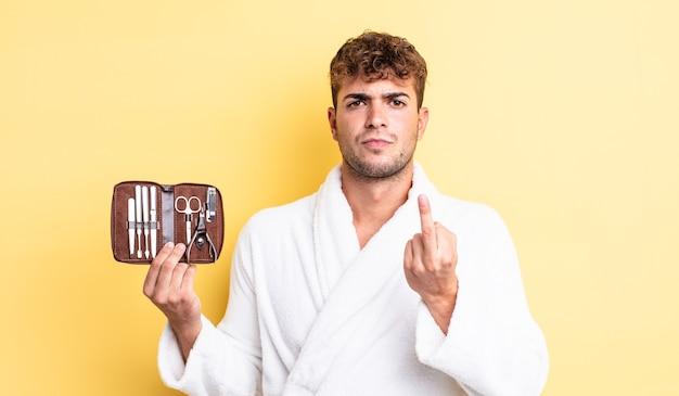 Jeune bel homme se sentant en colère, agacé, rebelle et agressif. concept de cas d'outils d'ongles