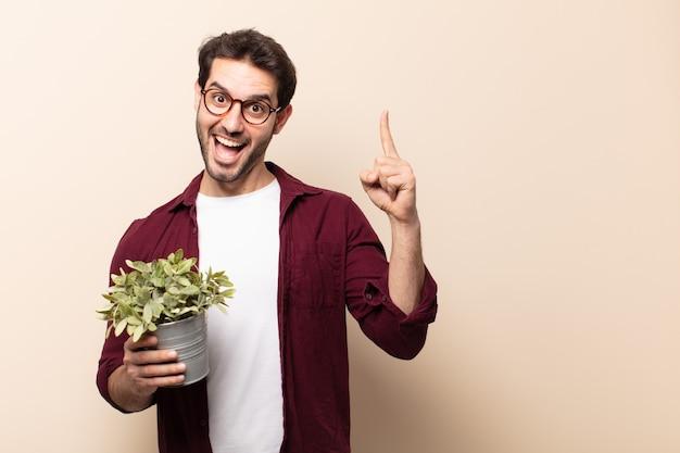 Jeune bel homme se sentant comme un génie heureux et excité après avoir réalisé une idée, levant joyeusement le doigt, eureka!