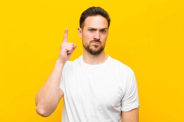 Jeune bel homme se sentant comme un génie tenant fièrement le doigt en l'air après avoir réalisé une excellente idée, disant eureka sur le mur orange