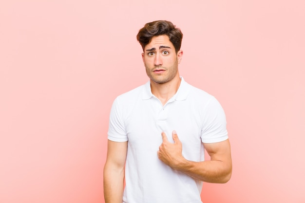 Jeune bel homme se sentant confus, perplexe et peu sûr, pointant vers soi se demandant et demandant qui, moi? contre le mur rose
